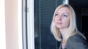 Ama de casa atractiva joven, situación rubia de la mujer cerca de la ventana abierta, mirando hacia fuera para alguien, agitando  almacen de metraje de vídeo