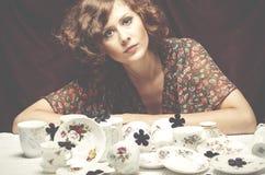 Ama de casa cansada Una mujer bonita que se sienta en una tabla con las porciones de Foto de archivo