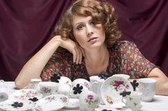 Ama de casa cansada Una mujer bonita que se sienta en una tabla con las porciones de servicio de café de los platillos de las taz Imagenes de archivo