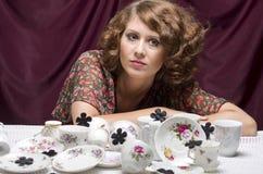 Ama de casa cansada Una mujer bonita que se sienta en una tabla con las porciones de servicio de café de los platillos de las taz Imágenes de archivo libres de regalías