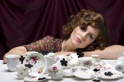 Ama de casa cansada Una mujer bonita que se sienta en una tabla con las porciones de servicio de café de los platillos de las taz Fotos de archivo libres de regalías