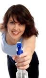 Ama de casa con la botella de la limpieza en el backround blanco Imagen de archivo