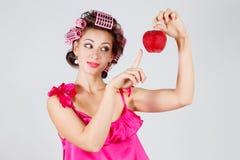 Ama de casa con los bigudíes en un camisón rojo y una manzana en su mano Fondo gris Imagen de archivo