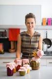 Ama de casa con los tarros de verduras conservadas en vinagre Imagen de archivo