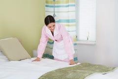 Ama de casa de sexo femenino que arregla la cama fotografía de archivo