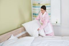 Ama de casa de sexo femenino que arregla las almohadas blancas en cama foto de archivo libre de regalías