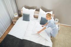 Ama de casa de sexo femenino que hace la cama con ropa de la cama Imagen de archivo libre de regalías