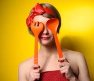 Ama de casa del estilo de Pinup con los utensilios de la cocina Foto de archivo