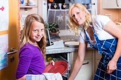 Ama de casa e hija con el lavaplatos Foto de archivo libre de regalías