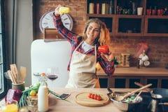 Ama de casa en auriculares y danza del delantal en cocina fotografía de archivo