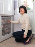 Ama de casa en la cocina cerca del congelador foto de archivo