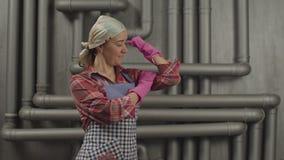 Ama de casa en los guantes de goma que muestran fuerza muscular almacen de video