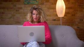 Ama de casa en suéter rosado en el funcionamiento del sofá atento con el ordenador portátil que es concentrado y que sonríe en la almacen de video