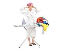 Ama de casa enfadada con la tarjeta que plancha y la ropa Fotografía de archivo