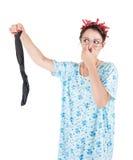 Ama de casa estereotípica divertida con olor del calcetín del hombre el mún fotografía de archivo