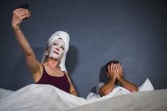 Ama de casa excéntrica con la máscara facial y la toalla del maquillaje que toman el selfie en cama y marido con la expresión des foto de archivo