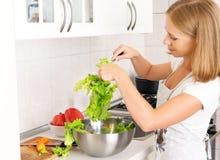 Ama de casa feliz de la mujer que prepara la ensalada en la cocina Imagen de archivo