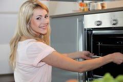 Ama de casa feliz hermosa que cocina una comida Foto de archivo