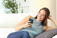 Ama de casa feliz que usa un teléfono móvil en un sofá Fotografía de archivo libre de regalías