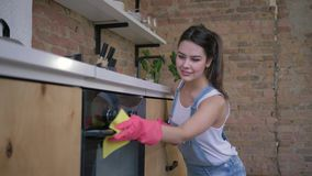 Ama de casa feliz, retrato del ama de casa sonriente femenino en los guantes de goma durante la limpieza general de la cocina y metrajes