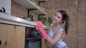 Ama de casa feliz, retrato de la feliz mujer del ama de casa en los guantes de goma durante la limpieza general de la cocina y ho almacen de metraje de vídeo
