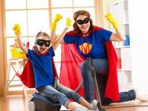 Ama de casa fuerte del super héroe e hija del niño lista a la limpieza del sitio Concepto del quehacer doméstico y del hogar Imagen de archivo libre de regalías