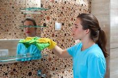 Ama de casa hermosa que hace la limpieza en el cuarto de baño imagenes de archivo