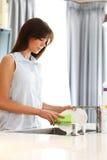 Ama de casa hermosa que hace platos Imagen de archivo