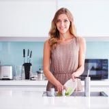 Ama de casa hermosa que hace platos Imagen de archivo libre de regalías