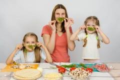 Ama de casa joven con dos hijas que se divierten que sostiene la puntilla del perejil como bigote en la tabla de cocina al compar Fotos de archivo libres de regalías