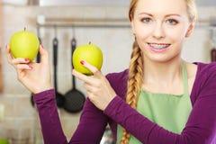 Ama de casa joven de la mujer en cocina con la fruta de la manzana Fotos de archivo
