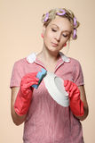 Ama de casa joven divertida con los guantes que llevan a cabo el scrubberr Foto de archivo libre de regalías