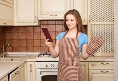 Ama de casa joven en delantal con la tableta picosegundo y guantes del horno en la k Imagen de archivo