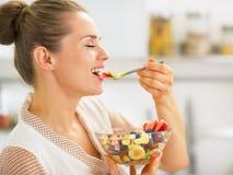 Ama de casa joven feliz que come la ensalada de fruta fresca en cocina Imagen de archivo