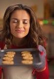 Ama de casa joven feliz que goza del olor de las galletas de la Navidad en la cacerola fotografía de archivo