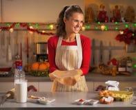 Ama de casa joven feliz que hace la pasta para las galletas de la Navidad Foto de archivo