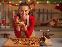 Ama de casa joven feliz que muestra el tarro con las nueces de la miel Foto de archivo libre de regalías