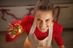Ama de casa joven feliz que muestra el tarro con las nueces de la miel Fotografía de archivo