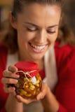 Ama de casa joven feliz que sostiene el tarro con las nueces de la miel Foto de archivo libre de regalías