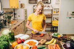 Ama de casa joven que cocina en la cocina, comida del eco imágenes de archivo libres de regalías
