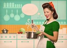 Ama de casa joven que cocina la sopa en su sitio de la cocina con el bub del discurso Fotos de archivo libres de regalías
