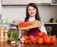 Ama de casa joven sonriente que cocina los tomates Fotografía de archivo
