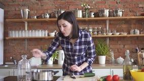 Ama de casa de la mujer en las verduras de los cortes de la cocina y la cena de los cocineros en la estufa que añade las especias almacen de video