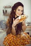 Ama de casa loca en cocina que sonríe comiendo las tortas Fotografía de archivo