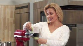 Ama de casa madura hermosa que usa la máquina de las pastas que hace las pastas hechas en casa almacen de metraje de vídeo