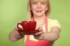 Ama de casa madura que da la taza de té Fotografía de archivo