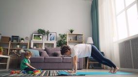 Ama de casa moderna que hace yoga mientras que su pequeño niño que juega con los bloques en la alfombra metrajes