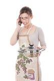 Ama de casa nerviosa en el delantal que sostiene el pote y que habla en móvil Fotografía de archivo libre de regalías