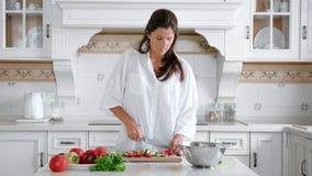 Ama de casa pensativa que prepara verduras del corte de la comida usando tiro medio del cuchillo y del tablero almacen de video