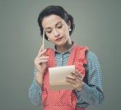 Ama de casa que anota una lista de compras Imagen de archivo libre de regalías
